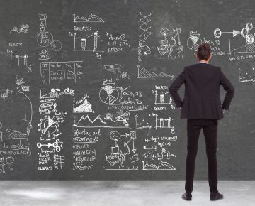 17243907 - back view of a business man  looking at some charts , graphs and calculations on a blackboard